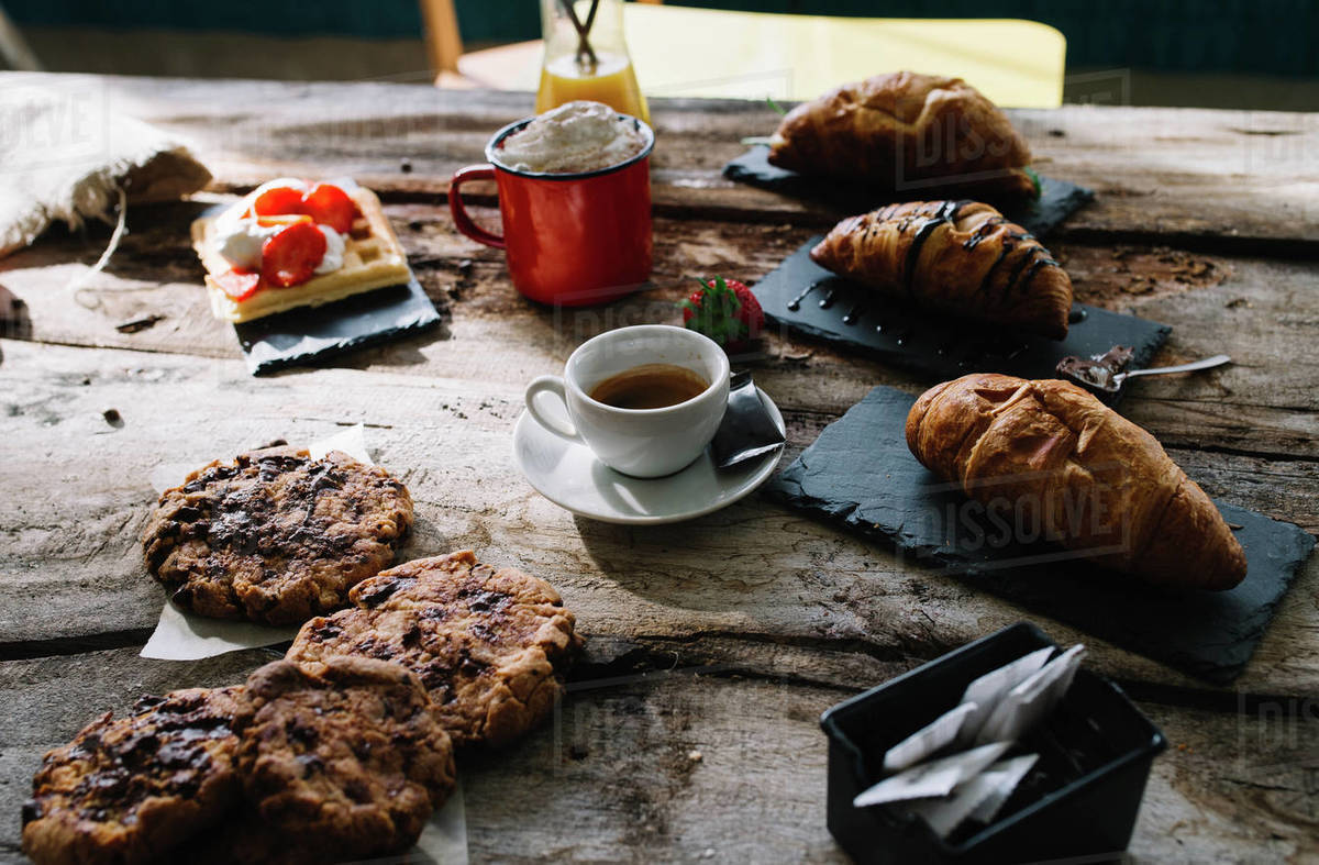 Croissant, coffee, cake, cream and raw strawberry on wooden table. Royalty-free stock photo