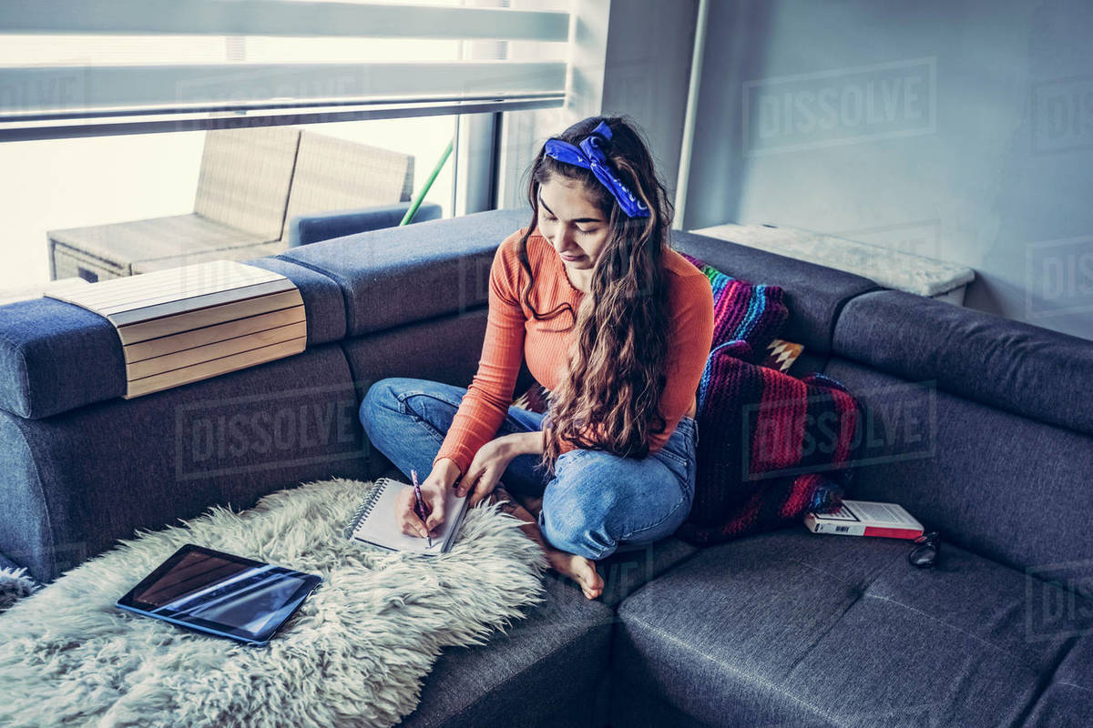Young casual woman is sitting on couch and writting in notebook Royalty-free stock photo