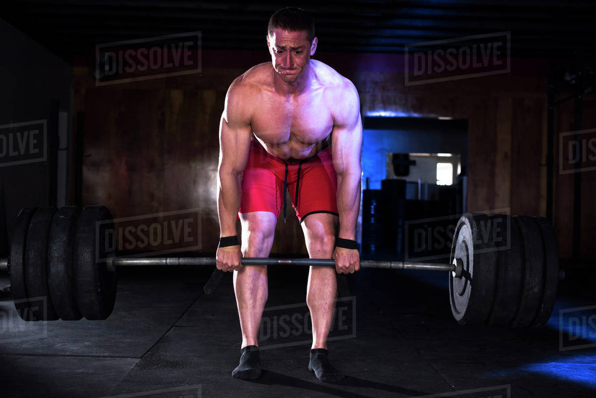 A shirtless body builder doing deadlifts at a warehouse gym Royalty-free stock photo