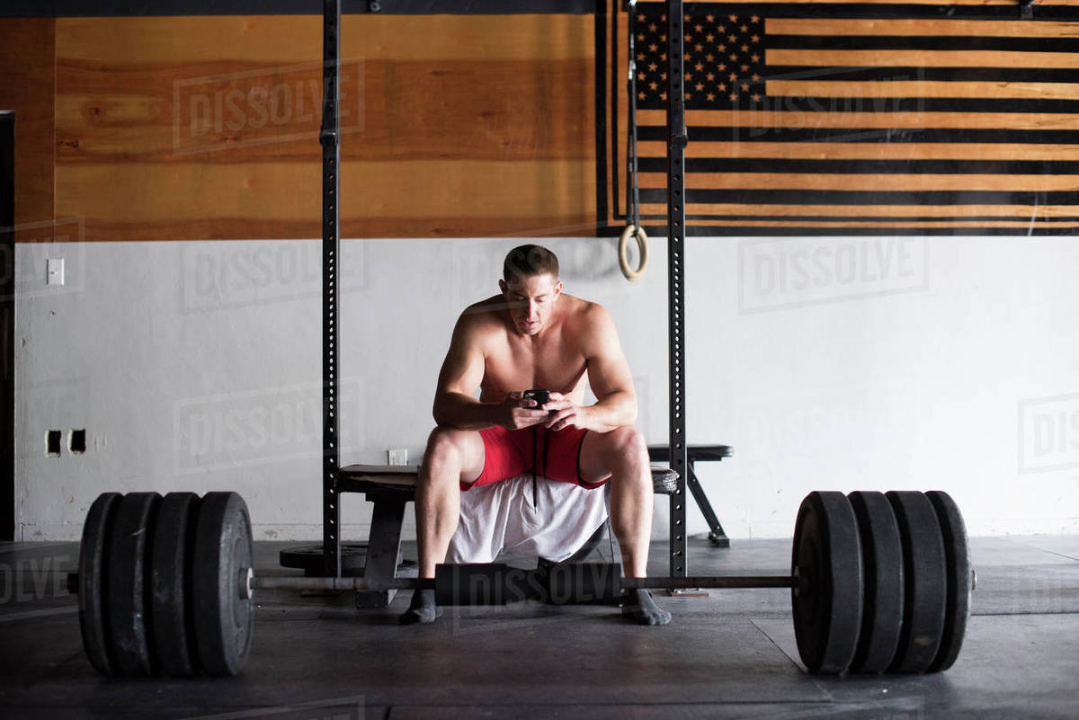 A weightlifter takes notes in his phone during a workout. Royalty-free stock photo