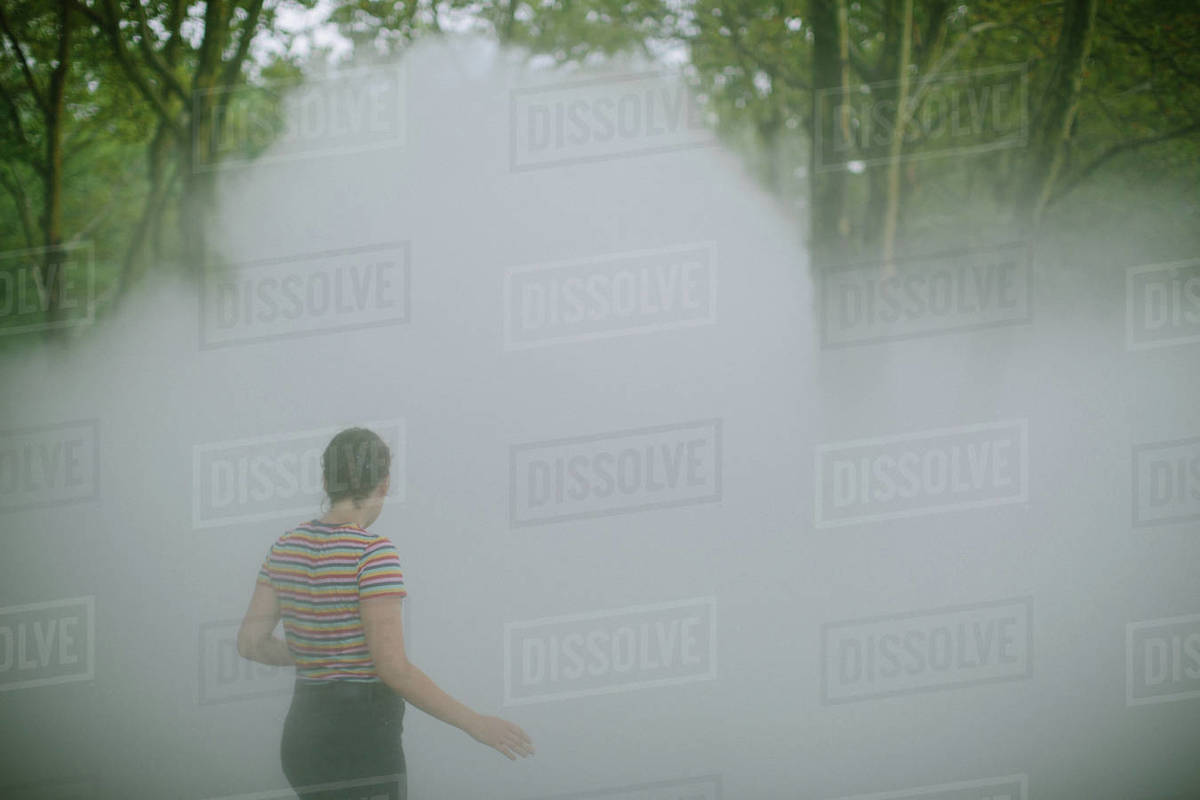 Young woman walking away through fog in a park Royalty-free stock photo