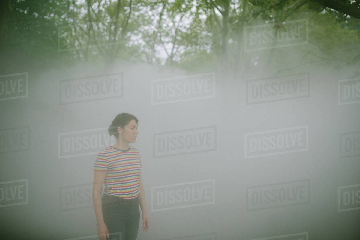 Young woman waiting in a foggy forest Royalty-free stock photo