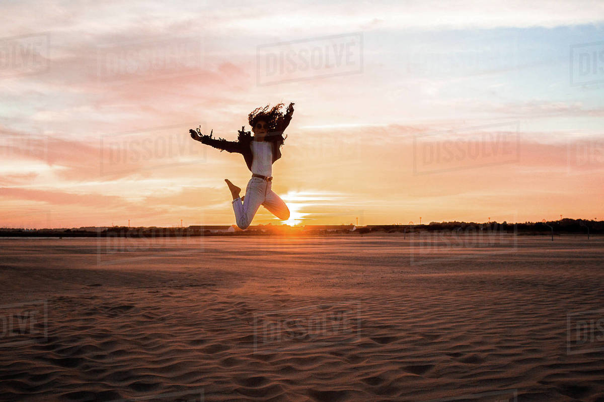 Woman jumping on the beach at sunset Royalty-free stock photo