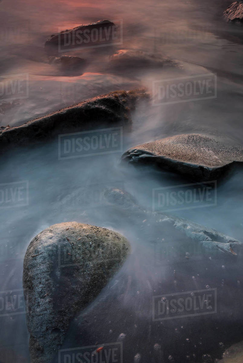 Waves wash around rocks reflecting the colors of sunset Royalty-free stock photo