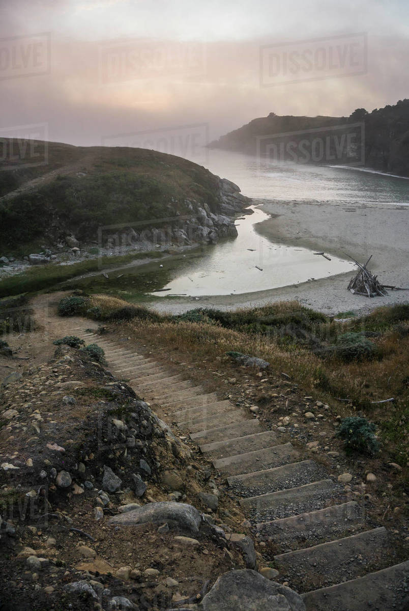 Stairs lead to a beach with fog and sunset Royalty-free stock photo