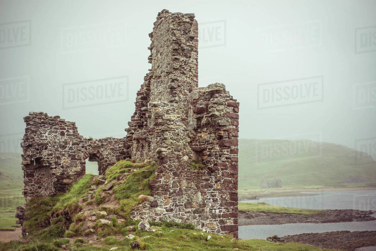 Castle ruins on moody loch water surrounded by misty mountains Royalty-free stock photo