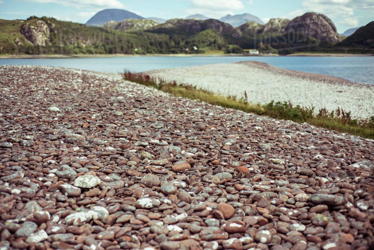 Pretty remote pebble stone beach with mountains Royalty-free stock photo