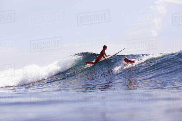 Friends surfboarding on wave in sea against sky Royalty-free stock photo