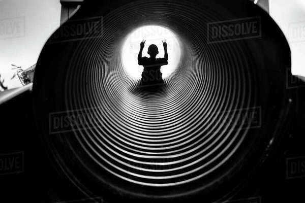 Silhouette boy gesturing while sliding tunnel slide Royalty-free stock photo