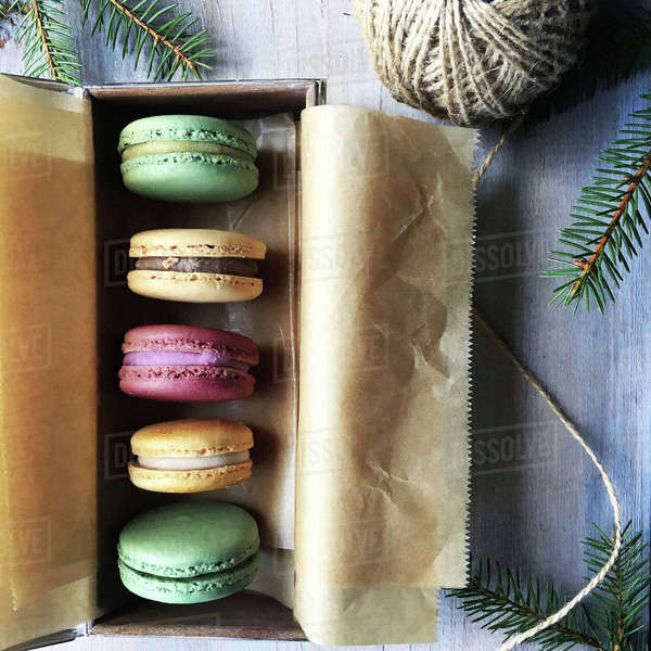 Overhead view of macaroons arranged in box with string and twigs on table Royalty-free stock photo