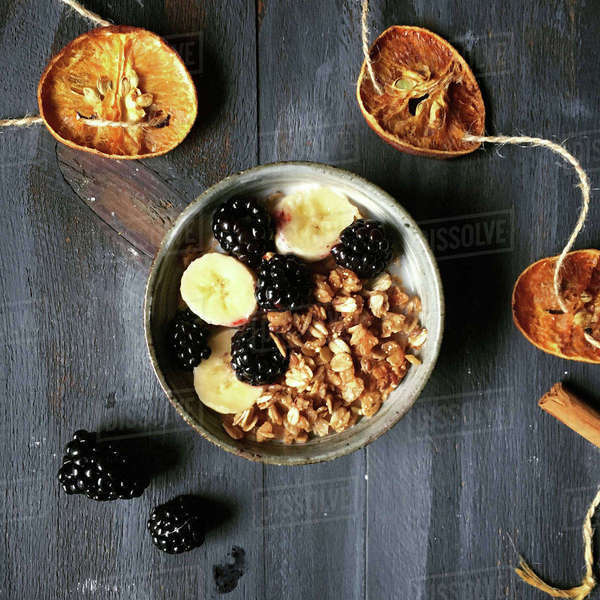 Overhead view of granola with fruits in bowl by garland on wooden table Royalty-free stock photo