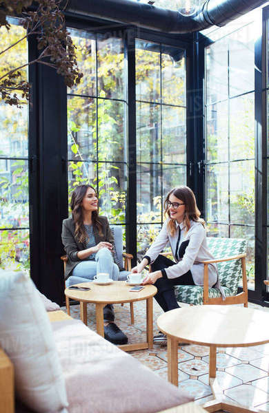 Businesswomen discussing while sitting in cafe Royalty-free stock photo