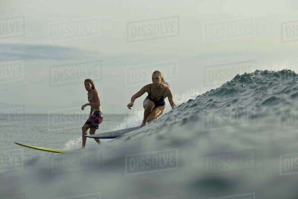 Friends surfing in sea against sky Royalty-free stock photo