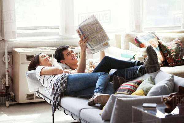 Happy couple reading newspaper while lying on sofa at home Royalty-free stock photo