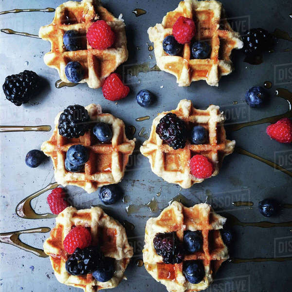 Overhead view of berry fruits and honey garnished on waffle Royalty-free stock photo