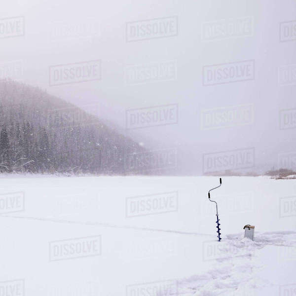 Ice auger on snow covered field during snowing Royalty-free stock photo