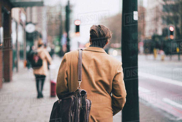 Rear view of man with shoulder bag walking on footpath in city Royalty-free stock photo