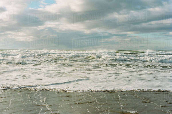 Scenic view of waves in sea against cloudy sky Royalty-free stock photo