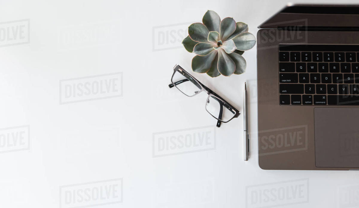 Overhead view of modern workspace with laptop, glasses and pen. Royalty-free stock photo