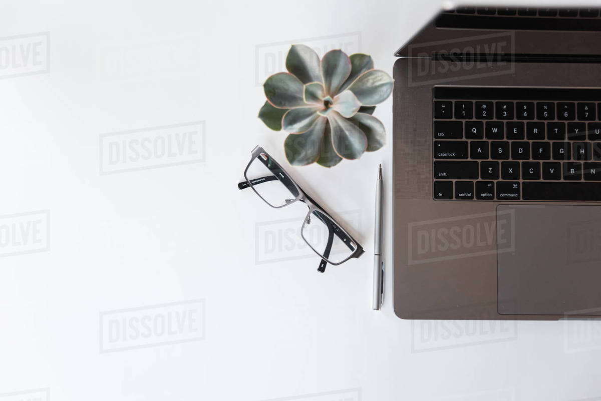 Overhead view of workspace with laptop, glasses, pen and plant. Royalty-free stock photo