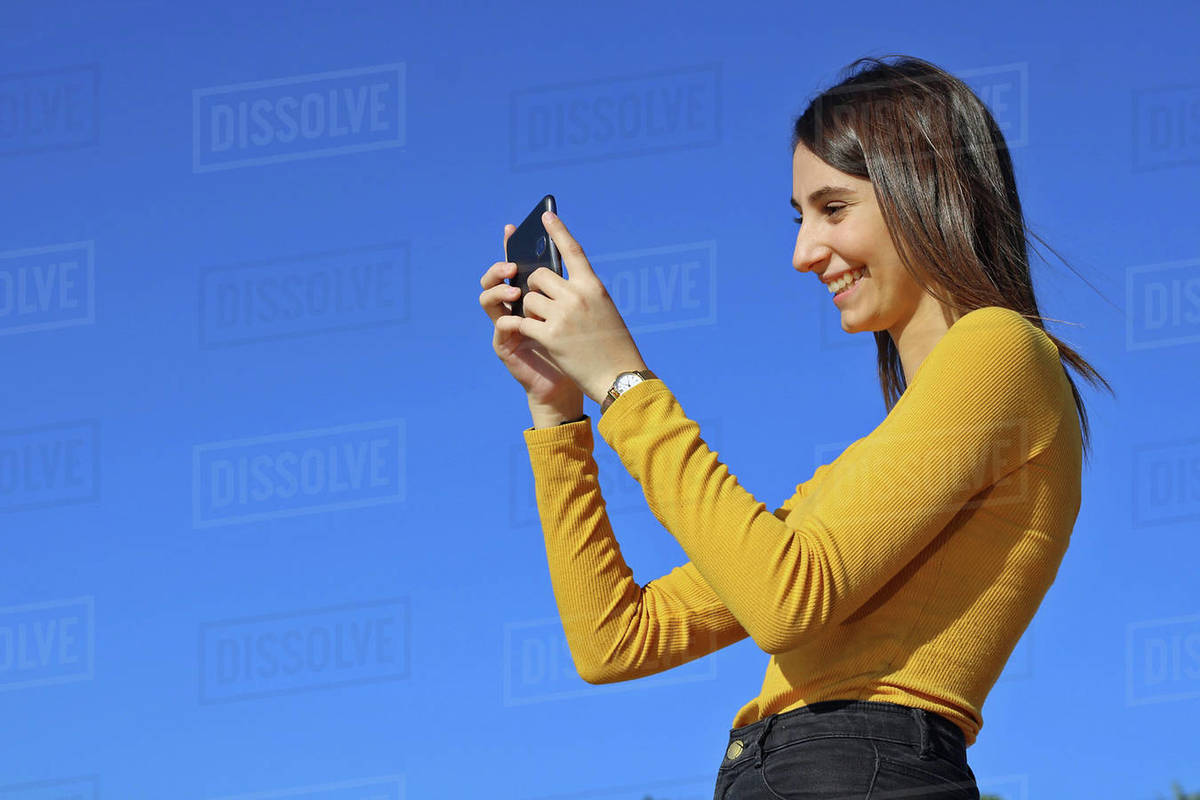 Beautiful girl dressed in yellow taking a picture with the phone Royalty-free stock photo
