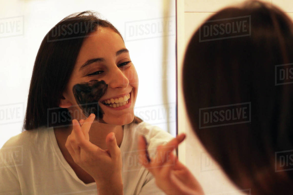Young and beautiful girl applying a brown sugar mask. Royalty-free stock photo