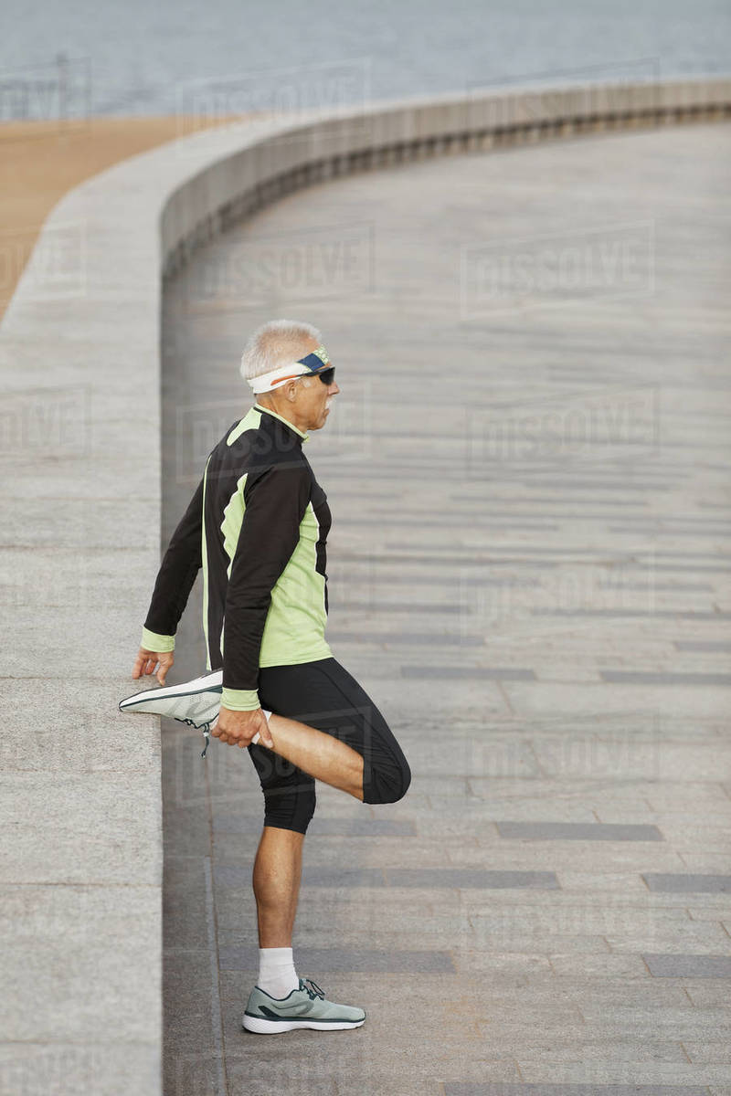Man Doing Leg Stretching Exercise Side View Royalty-free stock photo