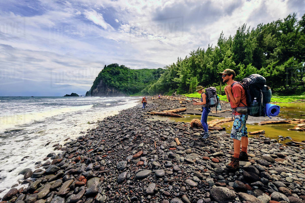 Backpackers stoping to take in the Pacific Ocean in the Pololu Valley Royalty-free stock photo