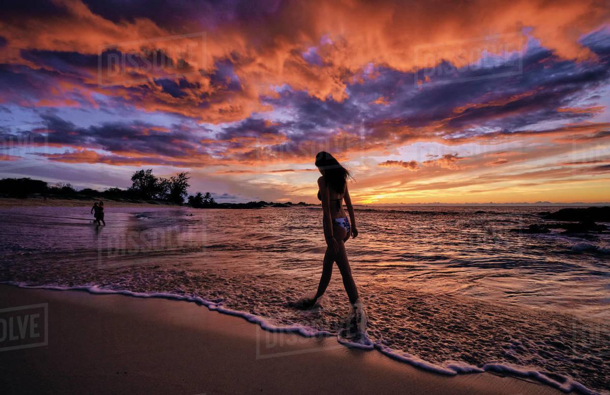 A young woman walks along Makalawena Beach on the Big Island of Hawaii Royalty-free stock photo
