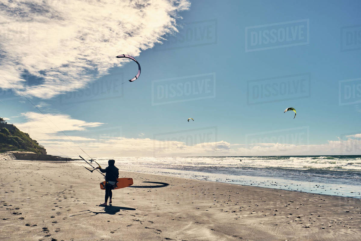 A kite surfer walks along a beach in Southern California, San Diego Royalty-free stock photo