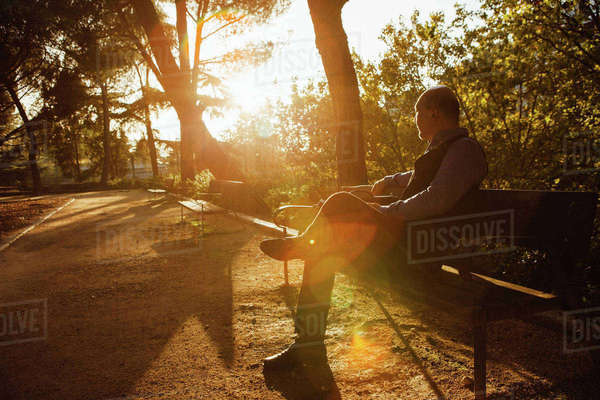 Side view of thoughtful man sitting on bench at park Royalty-free stock photo