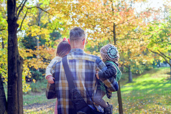 Rear view of father carrying daughters while walking in forest during autumn Royalty-free stock photo