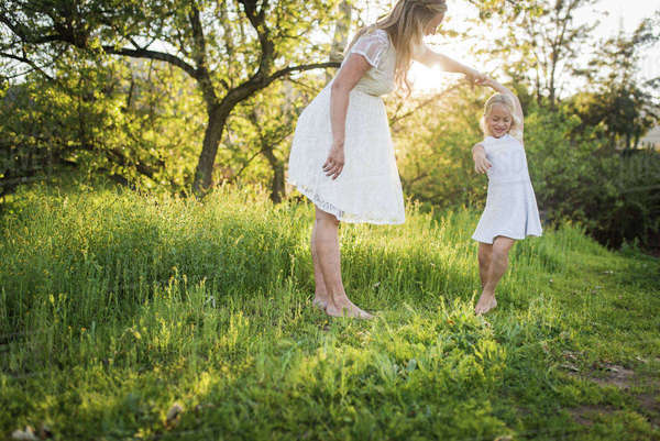 Pregnant mother dancing with daughter on grassy field in park Royalty-free stock photo