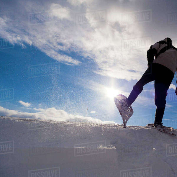 Low angle view of man snowshoeing on snow covered field against cloudy sky Royalty-free stock photo