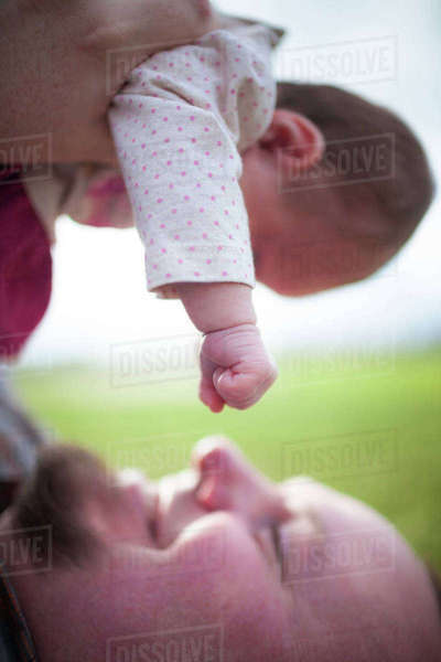 Close-up of playful father lifting daughter while lying on field in park Royalty-free stock photo