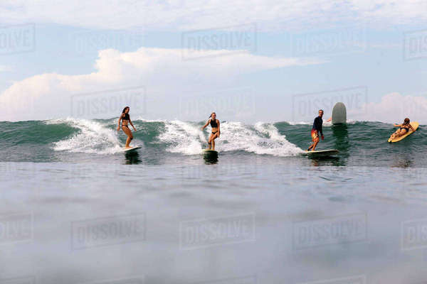 Friends surfing on sea against sky Royalty-free stock photo