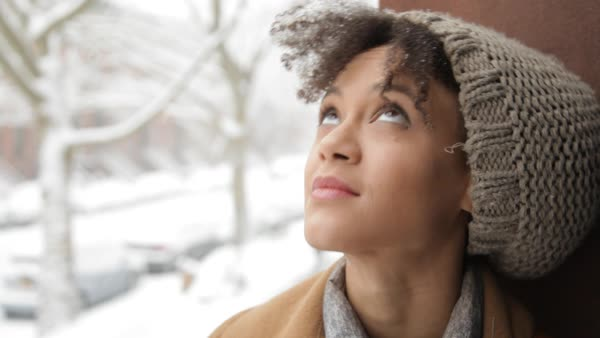 Handheld close-up of thoughtful woman looking away while relaxing by window during winter Royalty-free stock video