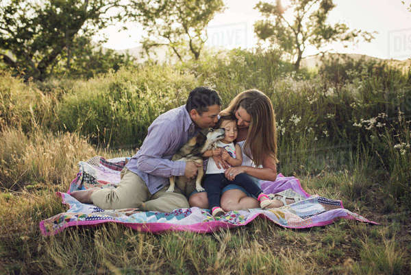 Happy family sitting on picnic blanket with dog at field Royalty-free stock photo
