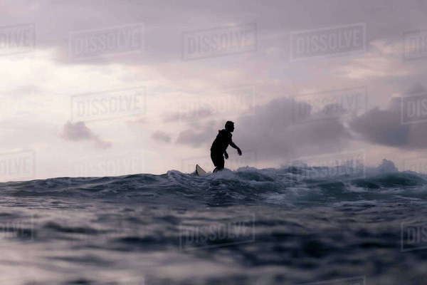 Silhouette man surfing in sea against cloudy sky Royalty-free stock photo