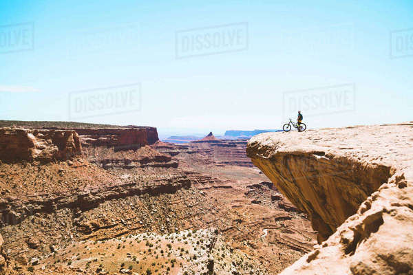 Mid distance of senior man standing with bicycle on cliff against clear sky Royalty-free stock photo
