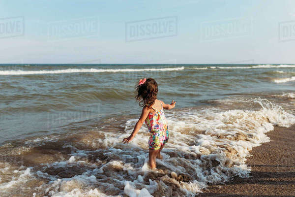 Carefree girl playing in waves at beach against clear sky Royalty-free stock photo