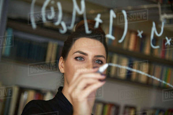Businesswoman writing formula on glass wall at office Royalty-free stock photo