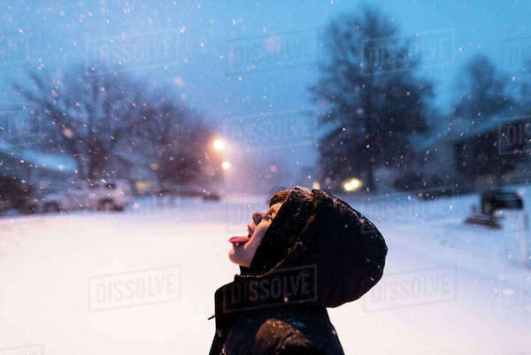 Playful boy catching snowflakes on tongue Royalty-free stock photo