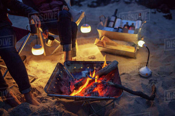 Low section of friends by bonfire at beach Royalty-free stock photo