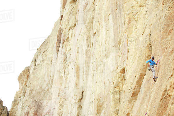 Low angle view of man rappelling down on mountain Royalty-free stock photo