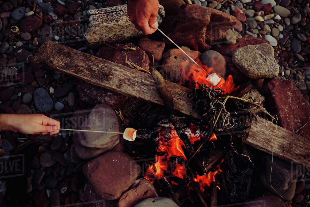 High Angle View Of Hands Roasting Marshmallows Over Campfire