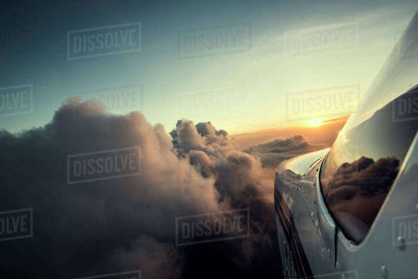 Close-up of airplane flying in cloudy sky during sunset Royalty-free stock photo