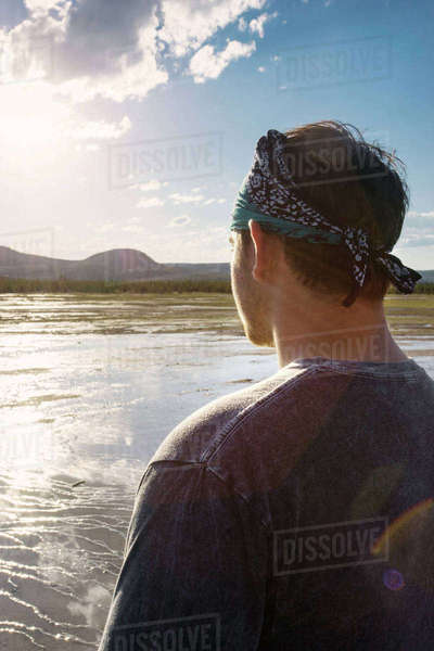 Rear view of man looking at view while standing against sky Royalty-free stock photo