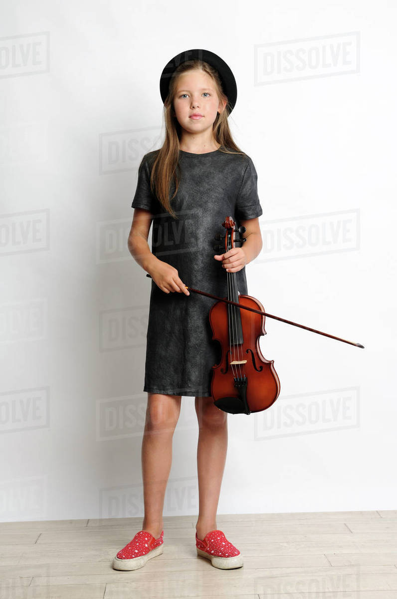 Portrait of girl holding violin while standing by wall at home stock photo