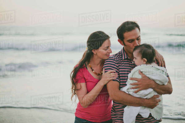 Woman looking at husband kissing son at beach Royalty-free stock photo